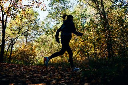personas trotando: corredor caucásico mujer corriendo en el parque de otoño, silueta fuera de foco