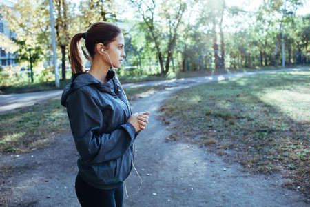 cool: sporty woman wearing hood jacket and listening music outdoors in the park, cool toned image