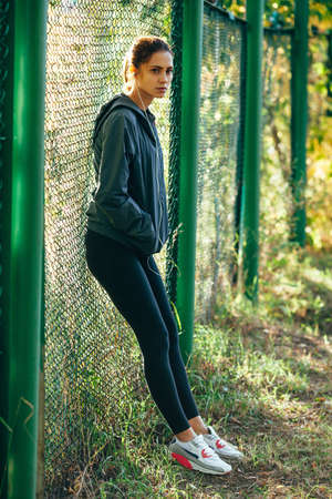 mesh: sporty woman wearing  jacket and listening music outdoors in the park, standing near mesh fence