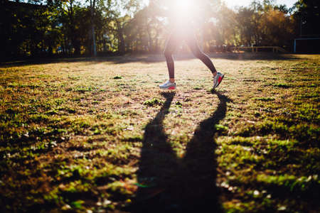 running woman  on sport yard against the sun, shadow on the grass, crop without head, big shadow on grass