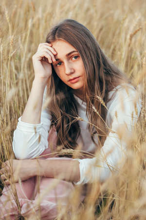 woman in field: Young beautiful woman wearing white  and pink dress sitting in wheat field