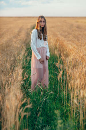 girls naked: happy beautiful brunette smiling girl posing in wheat field at sunset