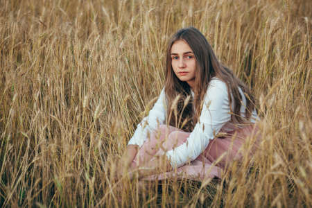 seriously: Young beautiful woman wearing white  and pink dress sitting in wheat field