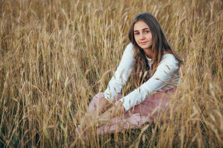 looking to camera: Young beautiful smiling girl wearing white  and pink dress sitting in wheat field