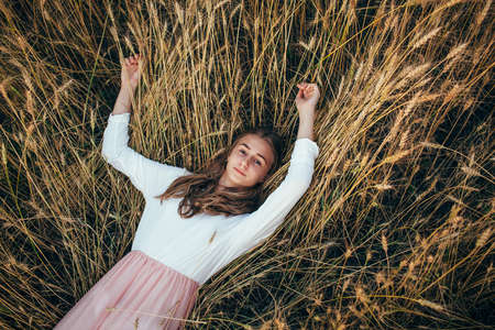 woman dress: Young beautiful happy woman wearing white  and pink dress lying in wheat field, looking at camera