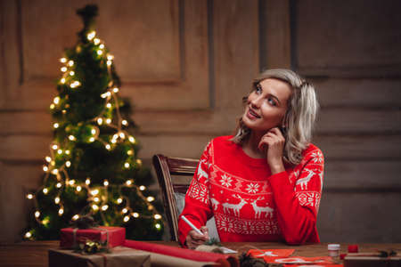 woman sweater: blonde woman thinking about words on christmas postcard Stock Photo