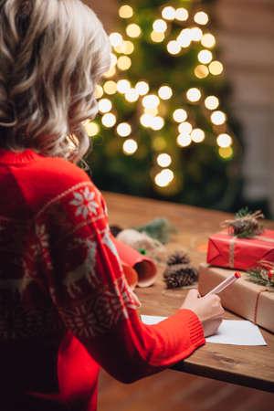 persona escribiendo: mujer rubia que llevaba suéter rojo con ciervos escribir palabras en la postal de Navidad, vista posterior, estilo rústico