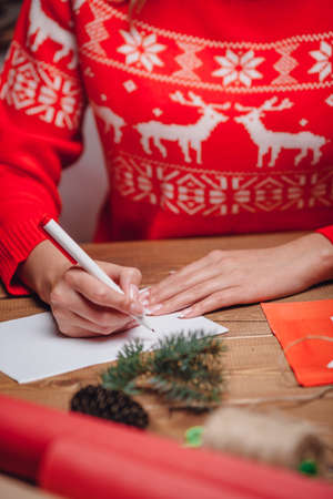 letter writing: woman hands writing on christmas postcard, closeup hands