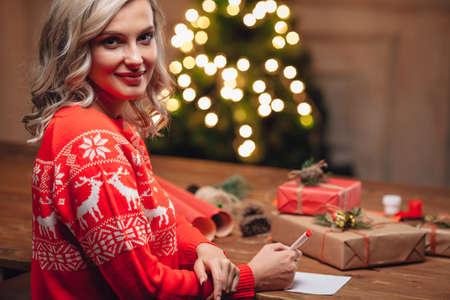rubia: Mujer rubia llevaba suéter rojo de escritura en la postal de navidad