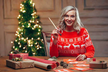 painting style: woman painting christmas flags with brush looking at camera, rustic style Stock Photo