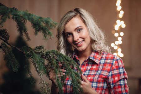 decorating christmas tree: beautiful blonde woman decorating Christmas tree, rustic style Stock Photo