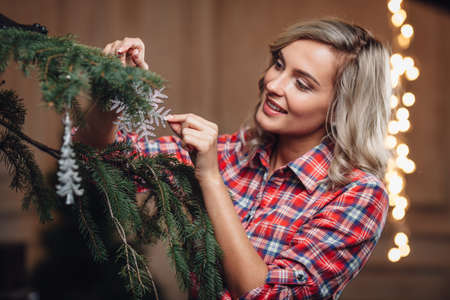 young tree: beautiful blonde woman decorating Christmas tree, rustic style Stock Photo