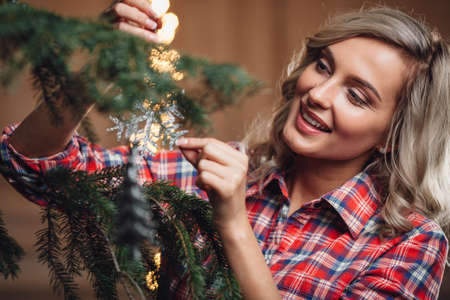 decorating: beautiful blonde woman decorating Christmas tree, rustic style Stock Photo