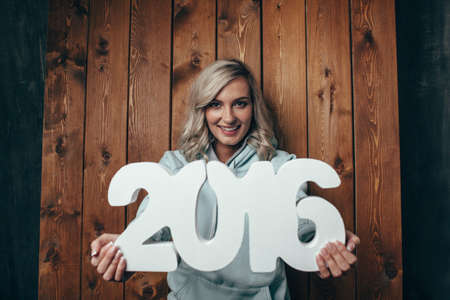 cute blonde: happy blonde woman holding 2016 numbers, rustic style , word happy on background Stock Photo