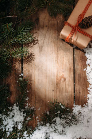 fur tree: gift box and fur tree under snow on old wooden background, rustic syle, top view, copy space in centre