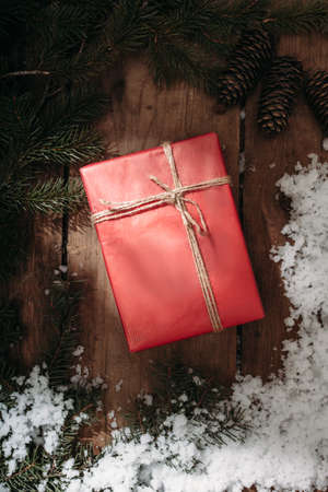under tree: red gift box and fur tree under snow on old wooden background, rustic syle, top view Stock Photo