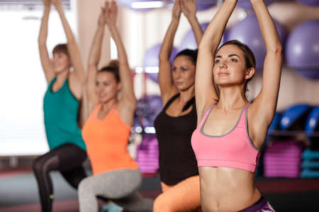 team hands: group of women working out in gym, they rising up hands