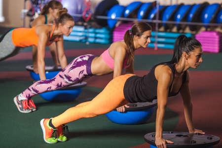push ups: group of female women balancing on bosu ball in push ups position