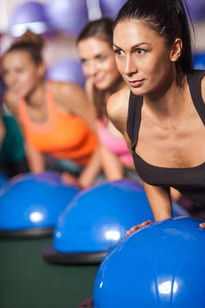 brunette woman: group of female women balancing on bosu ball in push ups position, close up image