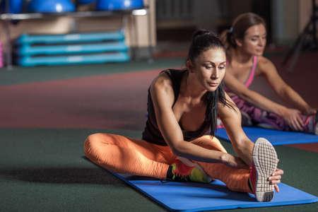 estiramiento: Mujeres estirar las piernas en el suelo en el gimnasio
