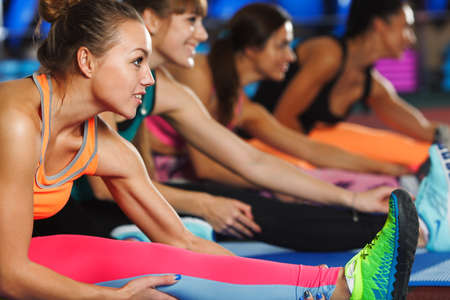 sport fitness: four sporty women stretching legs on the mats in the gym