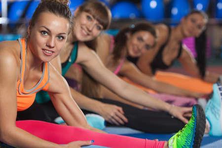 mujeres sentadas: cuatro mujeres deportistas que estiran las piernas en las esteras en el gimnasio Foto de archivo