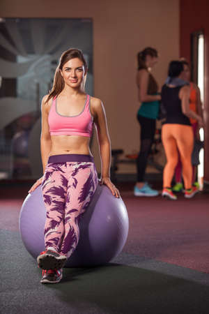 fitball: young adult sporty woman posing on fitball in the gym