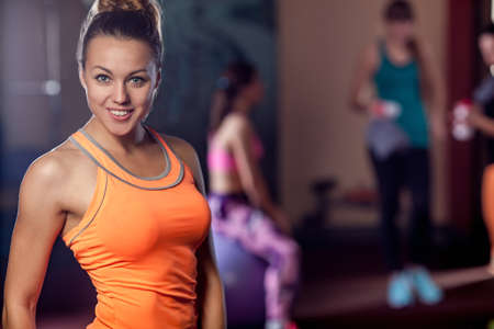 WOMAN FITNESS: young adult sporty woman posing in the gym