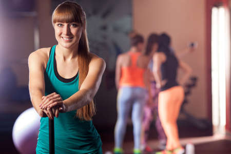young adult woman: young adult sporty woman posing with body bar in the gym Stock Photo
