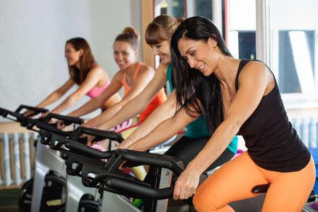 ciclos: Grupo de cuatro mujeres en el gimnasio, ejercer sus piernas sobre los ciclos