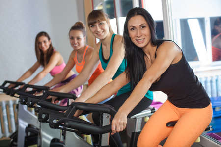 cycles: Group of four woman in the gym, exercising their legs on cycles