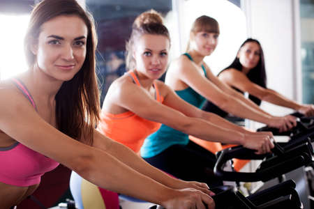 cycles: Grupo de cuatro mujeres en el gimnasio, ejercer sus piernas sobre los ciclos, vista closup