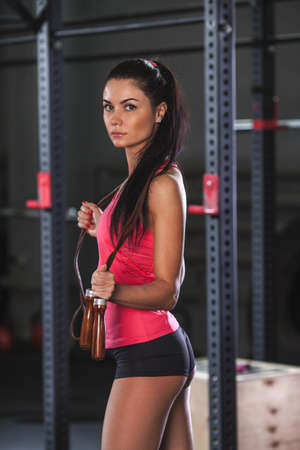 looking into camera: brunette woman standing in the gym and holding jumping rope and looking into  camera