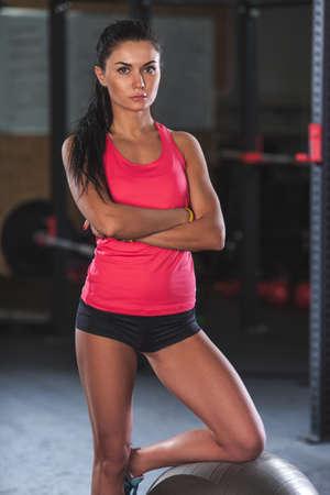 mujer morena posando con fitball en el gimnasio, en la bola de la rodilla