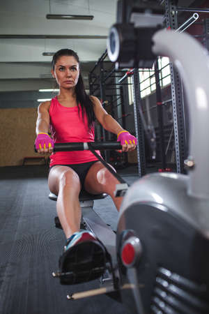 concetrated: caucasian sporty woman workout on rowing machine in gym