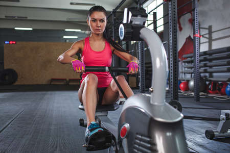 concetrated: caucasian sporty woman workout on rowing machine in gym, horizontal frame Stock Photo