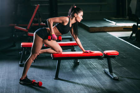 row: brunette woman exercising red dumbbell row at the gym