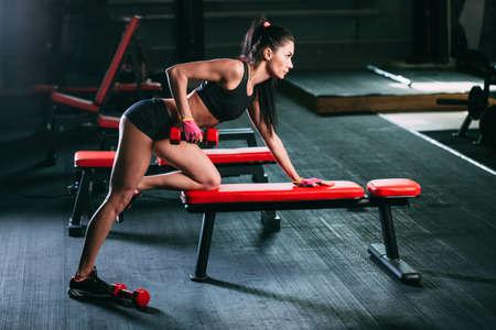 hilera: mujer morena ejercicio fila de color rojo pesa en el gimnasio Foto de archivo