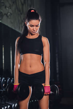 reflection mirror: caucasian brunette woman holding dumbbells in gym