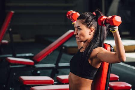 Junge, sportliche Frau, die Übungen mit Hanteln in der Turnhalle, Hantel Bank tun Presse Standard-Bild - 55578320