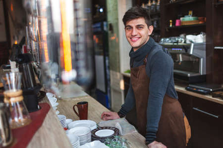 open business: Happy barista man portrait behind the bar in cafe Stock Photo