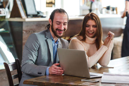 ice cram: young adult couple in a cafe looking to laptop Stock Photo