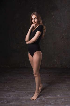 mujer sola: atractiva chica en traje negro en el estudio oscuro Foto de archivo