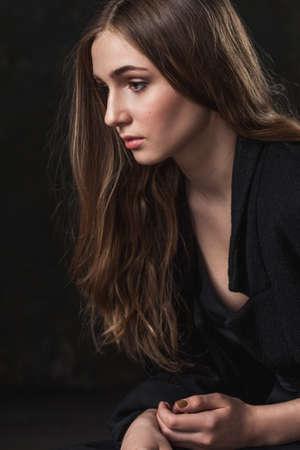 femme triste: portrait d'une jeune fille avec des yeux tristes sur fond sombre Banque d'images