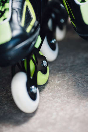 blading: green and white wheels of roller skates closeup