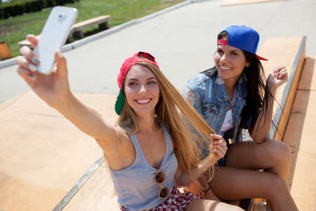 skate park: two girlfriends taking a selfie photo on the skate park with smartphone Stock Photo