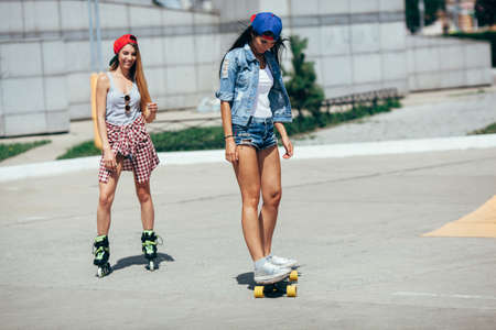 baseball hat: two young adult girls riding on the street at summer