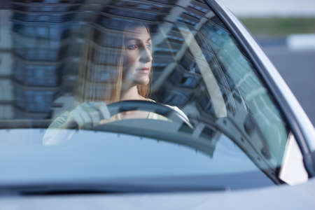 view from behind: young adult blonde beautiful woman driving a car, view from behind a glass