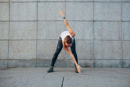 to incline: sporty woman doing stretching exercises incline outdoors Stock Photo