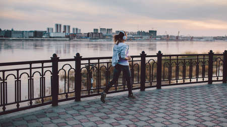 Young woman wearing headphones running in the city on river bank Stock Photo